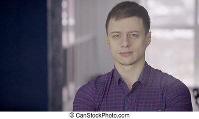 Portrait of a young European man in a blue checkered shirt....