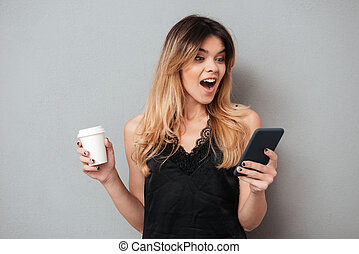 Portrait of a young excited woman looking at mobile phone