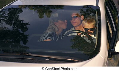 Portrait of a young family in sunglasses with a child in the car during a trip.