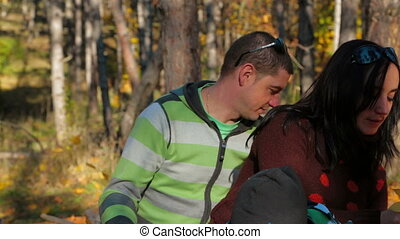 Portrait of a Young Family With a Child Picking Up Yellow Leaves In Autumn Park