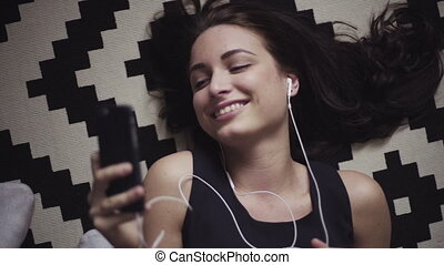 Portrait of a young female lying on the floor and talking on her mobile device or listening to the music with earphones plugged-in.