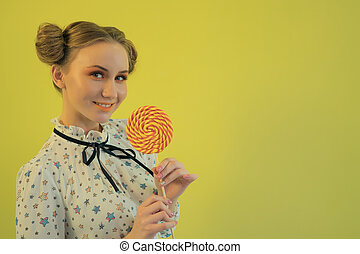 Portrait of a young funny bright smiling girl in a light shirt with a lollipop in the hand