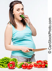 portrait of a young future mother with vegetables in the kitchen