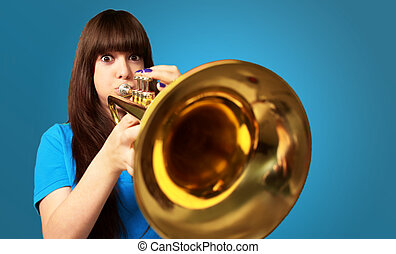 portrait of a young girl blowing trumpet on blue background