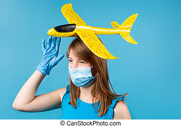 Portrait of a young girl in a medical mask and protective gloves holding a yellow toy plane on her head. Thinks about tourism and dreams of travel on a blue background.