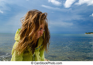 Portrait of a young girl in bathrobe on the beach, stormy weather in background.