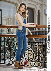 Portrait of a young girl in denim overalls