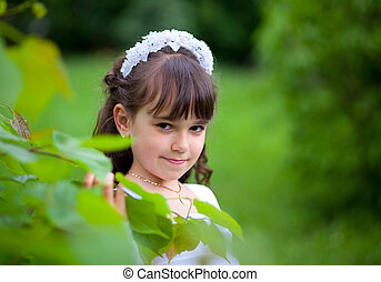 Portrait of a young girl in the park at summer