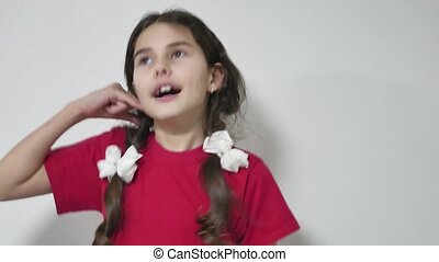 Portrait of a young girl kid showing call me sign. child gesture call me indoors