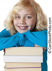 Portrait of a young girl leaning on a pile of books.
