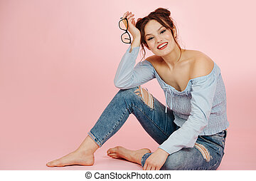 Portrait of a young girl sitting on a floor with glasses in hand. Over pink