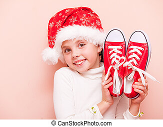 Portrait of a young girl with gumshoes and Santa Claus hat on pink background