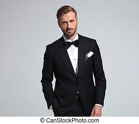 portrait of a young goom wearing tuxedo and bowtie, standing...