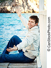 portrait of a young handsome man on the background of the sea