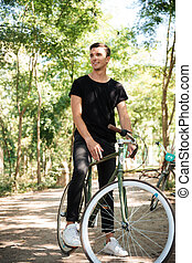 Portrait of a young handsome man riding on a bicycle