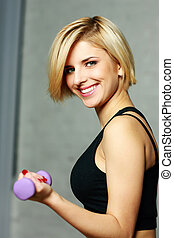 Portrait of a young happy fit woman doing workout with dumbbell