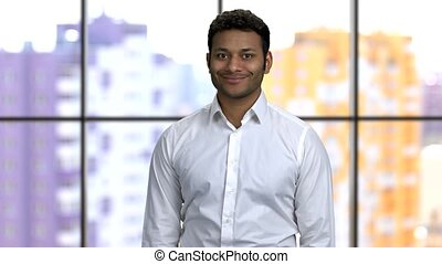 Portrait of a young happy hindu man wearing white formal shirt. Handsome brown-skinned guy indoors, window background.