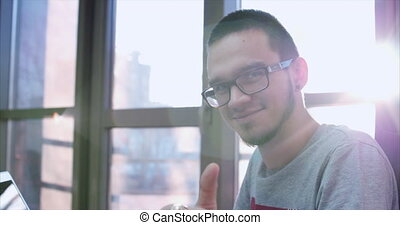 Portrait of a young happy man in glasses, businessman, programmer or trader, sitting in the office with laptop, looking at camera with sun shining behind, smiling happily, showing thumbs up. 4K