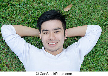 Portrait of a young happy man relaxing on the grass with his hands under the head