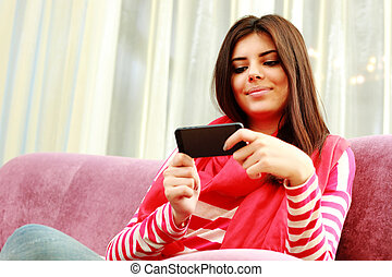 Portrait of a young happy woman using smartphone at home