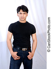 portrait of a young indian man wearing black t-shirt and dark blue jeans