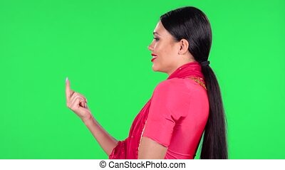 Portrait of a young Indian woman in national classic red sari is looking straight and coquettishly smiling, showing gesture come here. Side view. Green screen.