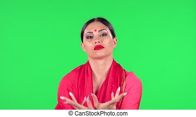 Portrait of a young Indian woman in national classic red sari is looking straight and dancing. Green screen.