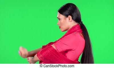Portrait of a young Indian woman in national classic red sari is looking straight and dancing. Side view. Green screen.