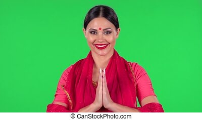 Portrait of a young Indian woman in national classic red sari is looking straight is smiles and folded palm to palm. Green screen.