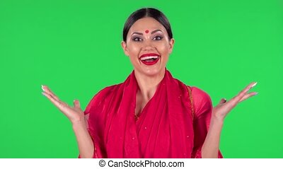 Portrait of a young Indian woman in national classic red sari is looking straight with shocked and surprised wow face expression. Green screen.