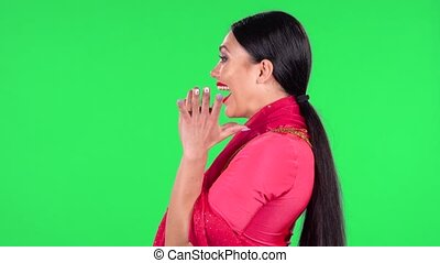 Portrait of a young Indian woman in national classic red sari is looking straight with very happy and joyful wow face expression. Side view. Green screen.