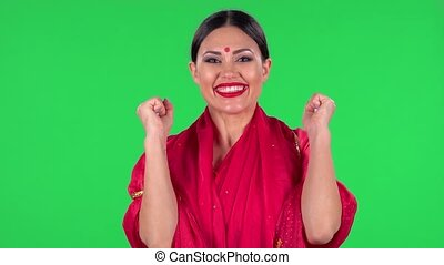 Portrait of a young Indian woman in national classic red sari is looking straight with very happy and joyful wow face expression. Green screen.