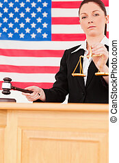 Portrait of a young judge knocking a gavel and holding scales of justice with an American flag in the background