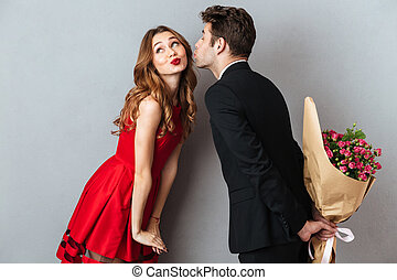 Portrait of a young lovely couple kissing while standing