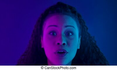 Portrait of a young lovely female African American looking at the camera with shocked and surprised wow face expression. Black woman with long curly hair poses against a dark studio. Close up face illuminated with purple and blue neon lights. Slow motion.