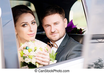 Portrait of a young loving couple newlyweds next to a bouquet in the window of a wedding car.
