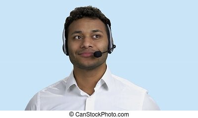 Portrait of a young male customer service operator. Handsome Indian consultant of call center talking with client on color background.