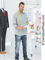 Portrait of a young male fashion designer holding sketch