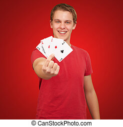 portrait of a young male holding four aces