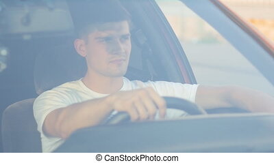 portrait of a young man behing the wheel, slow-motion