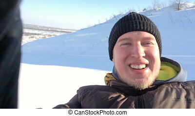 Portrait of a young man coming down the mountain in winter, smiling and looking at camera .