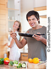 Portrait of a young man cooking while his wife is washing the dishes in their kitchen