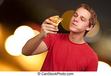 portrait of a young man eating pizza