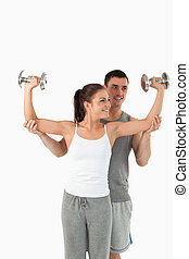 Portrait of a young man helping a gorgeous woman to work out