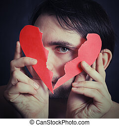 Portrait of a young man holding a paper broken heart