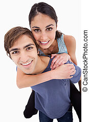 Portrait of a young man holding his girlfriend on his back