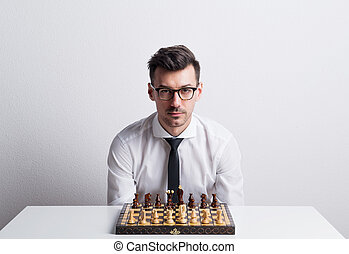 Portrait of a young man in a studio, sitting at the table with chess board game.