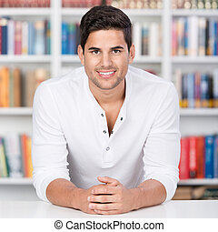 Portrait of a young man in front of bookshelf