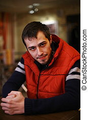 Portrait of a young man in red sporty vest. Shallow DOF, focus on eyes.