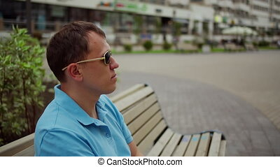 Portrait of a young man in sunglasses sitting on a street bench, side view, camera movement